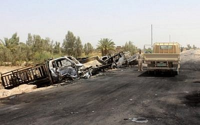 A member of the Iraqi government forces stands next to the charred vehicles on a road southwest of Fallujah after Iraqi forces airstrikes destroyed 260 vehicles carrying militants from the Islamic State group trying to flee after their defeat in Fallujah, June 29, 2016. (AFP/MOADH AL-DULAIMI)