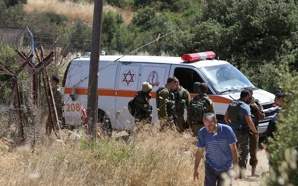 An ambulance and soldiers are seen outside a house in Kiryat Arba where a 13-year-old Israeli girl was stabbed to death in her bedroom by a Palestinian terrorist on June 30, 2016. (AFP/Menahem Kahana)