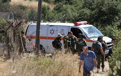 An ambulance and soldiers are seen outside a house in Kiryat Arba where a 13-year-old Israeli girl was stabbed to death in her bedroom by a Palestinian terrorist on June 30, 2016. (AFP PHOTO/MENAHEM KAHANA)