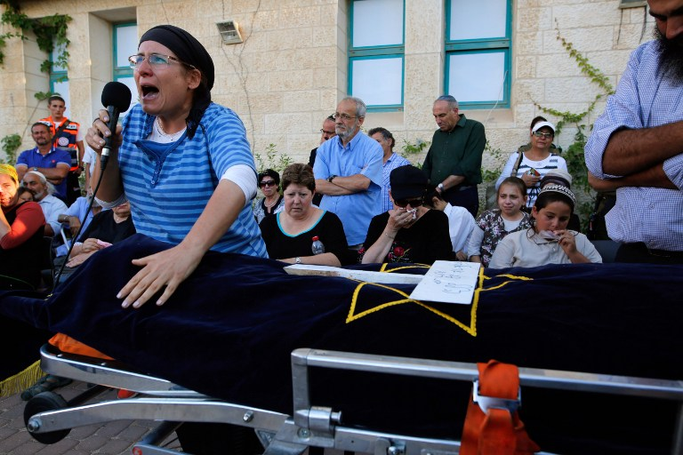Rina Ariel, mourns over the body of her daughter Hallel, a 13-year-old girl who was fatally stabbed by a Palestinian terrorist in her home, during her funeral in the Kiryat Arba settlement on June 30, 2016. (AFP PHOTO / GIL COHEN-MAGEN)