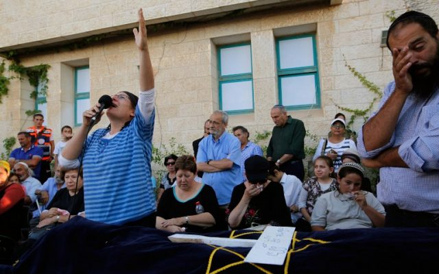 Rina Ariel mourns over the body of her daughter Hallel, a 13-year-old girl who was fatally stabbed by a Palestinian terrorist in her home, during her eulogy in the Kiryat Arba settlement on June 30, 2016. (AFP/Gil Cohen-Magen)