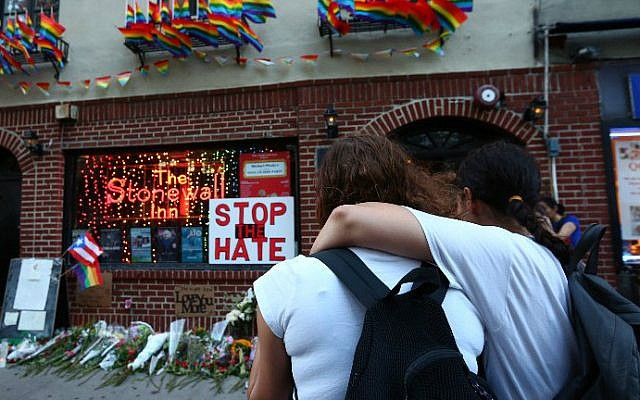 Women embrace before a make-shift memorial in front of the Stonewall Inn in New York City, where a vigil was held following the massacre that occurred at a gay Orlando nightclub on June 12, 2016. Monika Graff/Getty Images/AFP)