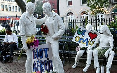 Tribute signs are placed on statues depicting homosexual couples in a park near the Stonewall Inn where a vigil was held following the massacre that occurred at a gay Orlando nightclub on June 12, 2016 in New York City. Monika Graff/Getty Images/AFP)