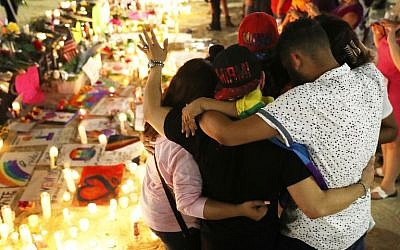 Mourners hug as they pay their respects at a memorial in front the Dr. Phillips Center for the Performing Arts for the victims of the Pulse gay nightclub shooting where Omar Mateen allegedly killed 49 people on June 13, 2016 in Orlando, Florida.  (Joe Raedle/Getty Images/AFP)