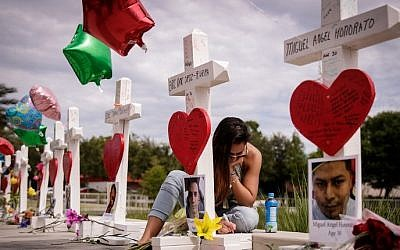 A woman writes a note on a cross at a memorial for each of the 49 victims of the Pulse Nightclub, next to the Orlando Regional Medical Center, June 17, 2016 in Orlando, Florida (Drew Angerer/Getty Images/AFP)