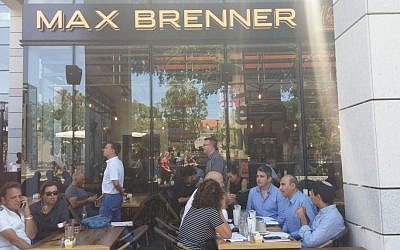 Customers sit at the Max Brenner cafe on June 9, 2016 where a day before, four people were killed in a shooting spree by two Palestinian cousins. (Ricky Ben-David)