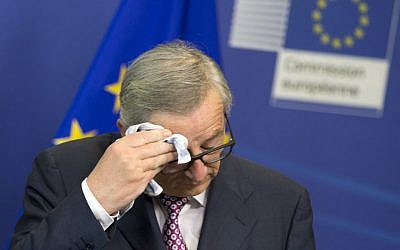 European Commission President Jean-Claude Juncker wipes his brow before speaking during a media conference at EU headquarters in Brussels on Wednesday, June 22, 2016. (AP Photo/Virginia Mayo)