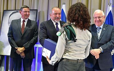 Defense Minister Avigdor Liberman awards an unnamed Military Intelligence officer with the Israel Defense Prize, alongside President Reuven Rivlin and Director-General of the Defense Ministry Udi Adam, left, during a ceremony at the President's Residence in Jerusalem on June 28, 2016. (Ariel Hermoni/Defense Ministry)