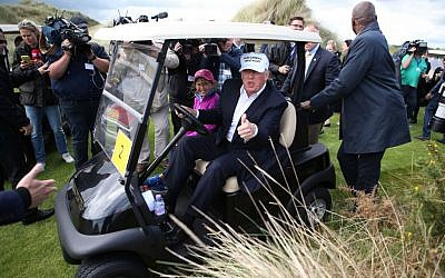 US presidential candidate Donald Trump chats with the watching media aboard a golf cart with granddaughter Kai after he arrived at the Trump International Golf Links at Balmedie, near Aberdeen, Scotland, June 25, 2016. (Andrew Milligan / PA via AP)