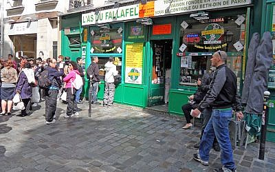 Yomi Peretz, right, approaching a line of tourists waiting to place their orders at The Falafel Ace in the historic Jewish quarter of Paris, April 2012. (WikiMedia Commons)