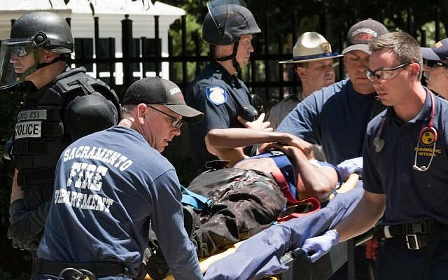 Paramedics rush a stabbing victim away on a gurney Sunday, June 26, 2016, after members of right-wing extremists groups holding a rally outside the California state Capitol building in Sacramento clashed with counter-protesters, authorities said. (AP/Steven Styles)