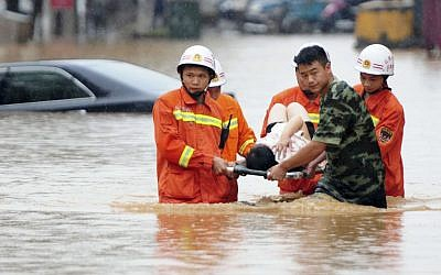 In this June 15, 2016 photo, rescuers carry a woman on a stretcher through a flooded area in Jiujiang in southern China's Jiangxi province. (Chinatopix via AP)