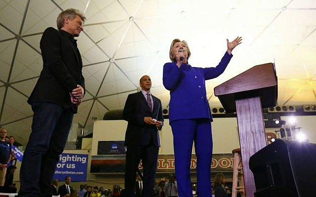 Democratic presidential candidate Hillary Clinton stands on stage with musician Bon Jovi, left, and Sen. Cory Booker, D-New Jersey, while speaking during a campaign stop at the Newark campus of Rutgers University, Wednesday, June 1, 2016, in Newark, New Jersey. (AP Photo/Julio Cortez)