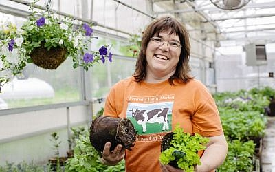 Theresa Freund holds plants growing in CowPots, a product made on the farm, in the Freund's Farm Market & Bakery's greenhouse. (Courtesy Cabot Creamery)