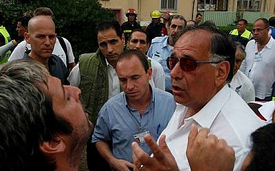 Haifa Mayor Yona Yahav (in white shirt), argues with a man in the city's Kiryat Eliezer neighborhood. (Phil Sussman /Flash90)