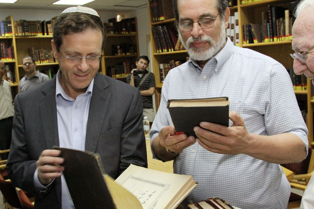 Opposition leader Isaac Herzog leafs through through Jewish holy books during a visit to the Har Etzion yeshiva in the West Bank settlement of Alon Shvut on April 29, 2014 (Gershon Elinson/FLASH90)