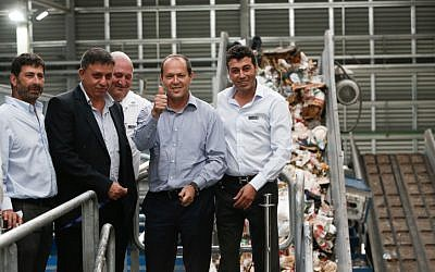 Jerusalem Mayor Nir Barkat (giving the thumbs-up) and ex-environmental protection minister Avi Gabbay (second from left) cutting the ribbon during the opening ceremony of the Greenet recycling plant in the Atarot industrial zone, north of Jerusalem, on June 16, 2015. (Yonatan Sindel/Flash90)