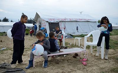 """Refugee children playing near a tent painted with the slogan """"We want go to Germany"""" in Idomeni refugee camp on May 1'st, 2016 (Photo Credit: Gili Yaari / Flash90)"""