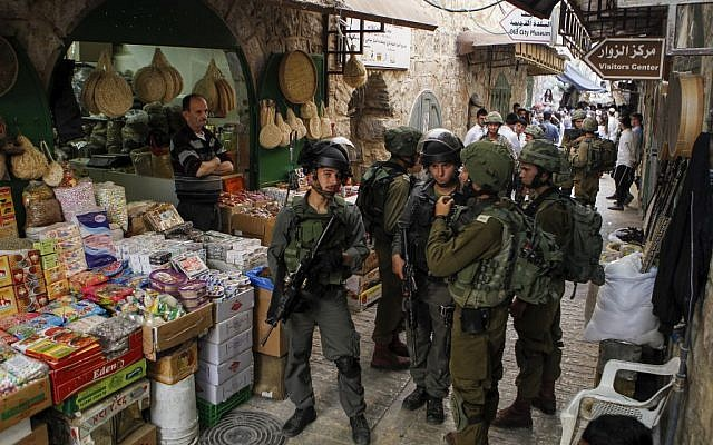 Israeli troops stand guard as settlers take a tour in the contested West Bank city of Hebron, on June 4, 2016. (Wisam Hashlamoun/Flash90)