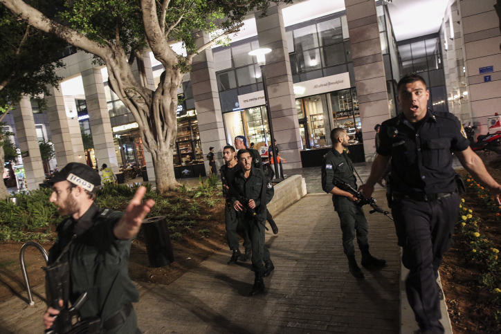 Israeli security forces at the scene where two terrorists opened fire at the Sarona Market shopping center in Tel Aviv, on June 8, 2016. (Miriam Alster/Flash90)