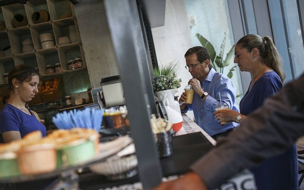 Opposition leader MK Isaac Herzog and his wife Michal show their support by buying coffee at the Sarona Market shopping center in Tel Aviv on June 9, 2016, the morning after a fatal terror attack at the site. (Miriam Alster/Flash90)