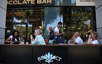Israelis seen eating at Benedict's restaurant at the Sarona Market shopping center in central Tel Aviv, June 9, 2016, the morning after a deadly terror attack at the site. (Miriam Alster/Flash90)