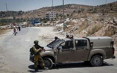 Israeli soldiers man a checkpoint at the entrance to the Palestinian village of Yatta in the southern West Bank on June 9, 2016. (Wisam Hashlamoun/Flash90)