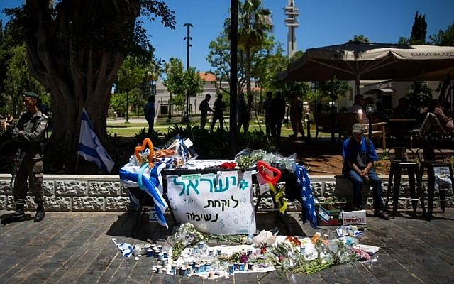 Flowers and candles are placed at a makeshift memorial at the site of a shooting attack at Sarona Market, Tel Aviv, on June 10, 2016, two days after Palestinian terrorists killed four Israelis. (Photo by Miriam Alster/Flash90)