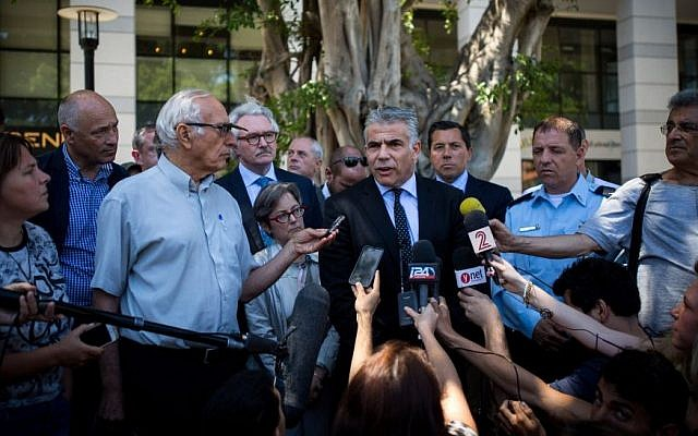 Leader of the Yesh Atid party Yair Lapid speaks to the press, along with foreign diplomats, after visiting the Max Brenner restaurant, the site of a June 8, 2016, terror attack, at Sarona Market, Tel Aviv, on June 10, 2016. (Miriam Alster/Flash90)