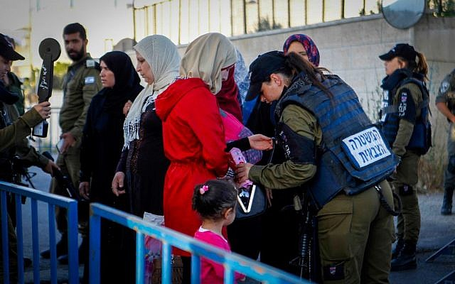 Palestinians pass through Israeli security at a checkpoint in the West Bank city of Bethlehem, as they head to Al-Aqsa Mosque in Jerusalem for the first Friday prayers of Ramadan, June 10, 2016. (Wisam Hashlamoun/Flash90)