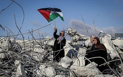The mother of Palestinian terrorist Murad Idais holds a Palestinian flag as she stands in the rubble of their house after it was demolished by the IDF in the West Bank village of Yatta, south of Hebron, on June 11, 2016. Idais stabbed mother-of-six Dafna Meir to death. (Wisam Hashlamoun/Flash90)