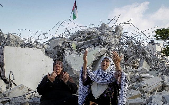 Family members of Palestinian terrorist Morad Adais are seen in the rubble of their house after it was demolished by Israeli forces in the West Bank village of Yatta, south of Hebron, on June 11, 2016 (Wisam Hashlamoun/Flash90)
