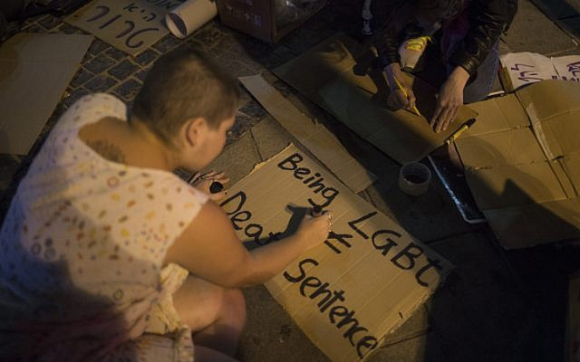 Young Israeli LGBT activists write signs as they gather at Zion Square in Jerusalem in solidarity with the victims of the shooting attack at a gay club in Orlando, USA, on June 12, 2016. (Hadas Parush/Flash90)