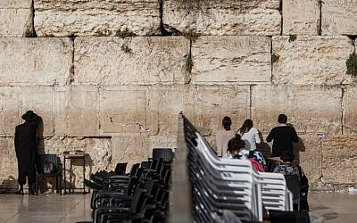 People pray on either side of the dividing wall that separates the male and female prayer sections at the Western Wall, June 14, 2016. (Wajsgras/Flash90)