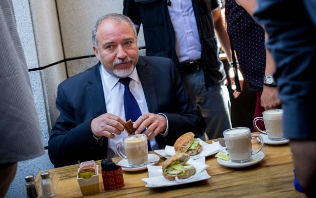 In a show of support a day after a deadly terror attack there, Defense Minister Avigdor Liberman has coffee at the Sarona Market in tel Aviv, on Thursday, June 9, 2016 (Miriam Alster/Flash90)