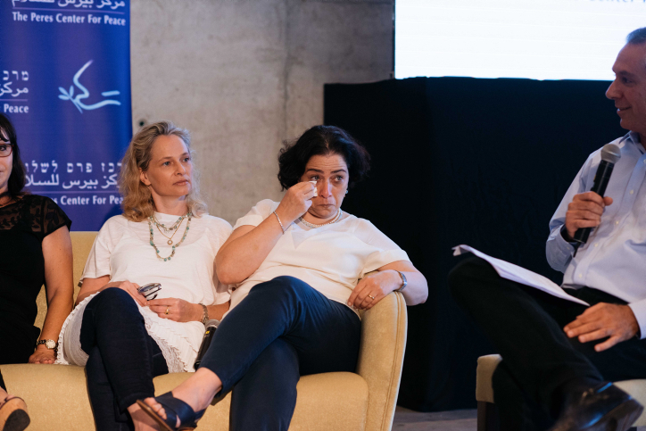 Survivor Dana Zuckerman cries next to fellow survivor Anat Brodesky Charniak during an event makring 40 years since Operation Thunderbolt, the Israeli rescue of over 100 hostages from the Entebbe Airport in Uganda on July 4, 1976, at the Peres Center for Peace in Jaffa on June 27, 2016. (Ben Kelmer/FLASH90)