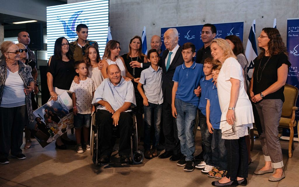 Survivors of Operation Thunderbolt, the Israeli rescue of over 100 hostages from the Entebbe Airport in Uganda on July 4, 1976, along with former Israeli president Shimon Peres and Dalia Rabin, a former member of Knesset and daughter of former prime minister Yitzchak Rabin, present Sorin Hershko with a certificate of appreciation during an event at the Peres Center for Peace in Jaffa marking 40 years since the kidnapping, on June 27, 2016. (Ben Kelmer/FLASH90)
