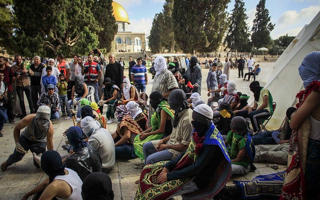 Masked Palestinians hold stones as they gesture during clashes with Israeli police during the holy month of Ramadan near Al-Aqsa Mosque on the Temple Mount in Jerusalem's Old City June 28, 2016. (Muammar Awad/Flash90)