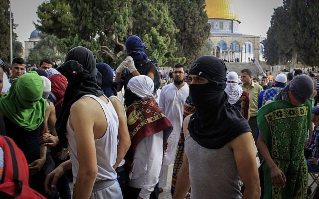 Masked Palestinians hold stones during clashes with Israeli police on the Temple Mount complex in Jerusalem's Old City, June 28, 2016. (Muammar Awad/Flash90)