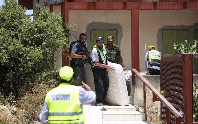 First responders remove a mattress from the home of 13-year-old Hallel Yaffa Ariel, who died of her wounds after she was stabbed by a Palestinian terrorist as she lay in bed at her home in Kiryat Arba, in the West Bank, June 30, 2016. (Hadas Parush/Flash90)