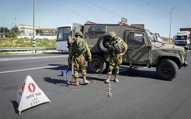 Israeli soldiers set up a checkpoint at the entrance to the Kiryat Arba settlement in the West Bank on June 30, 2016, after a Palestinian teenager stabbed and killed a 13-year-old Israeli girl there. (Wisam Hashlamoun/Flash90)