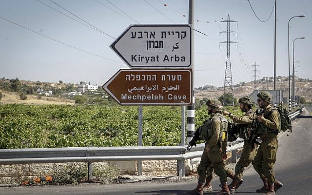 Israeli soldiers patrol the area around the entrance to the Kiryat Arba settlement in the West Bank on June 30, 2016, after a Palestinian teenager stabbed and killed a 13-year-old Israeli girl there. (Wisam Hashlamoun/Flash90)
