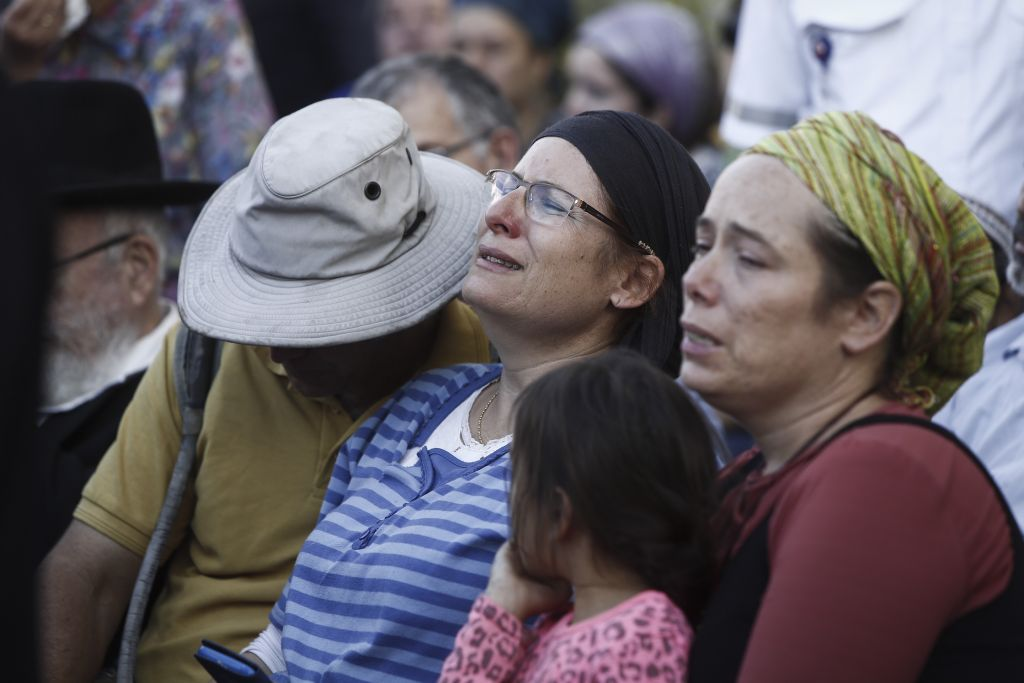The family of Hallel Yaffa Ariel mourn during her funeral ceremony in the Jewish settlement of Kiryat Arba, in the West Bank, on June 30, 2016. Earlier in the day, a 17-year-old Palestinian terrorist broke into their home and stabbed and killed 13-year-old Hallel as she slept in her bedroom. (Yonatan Sindel/Flash90)