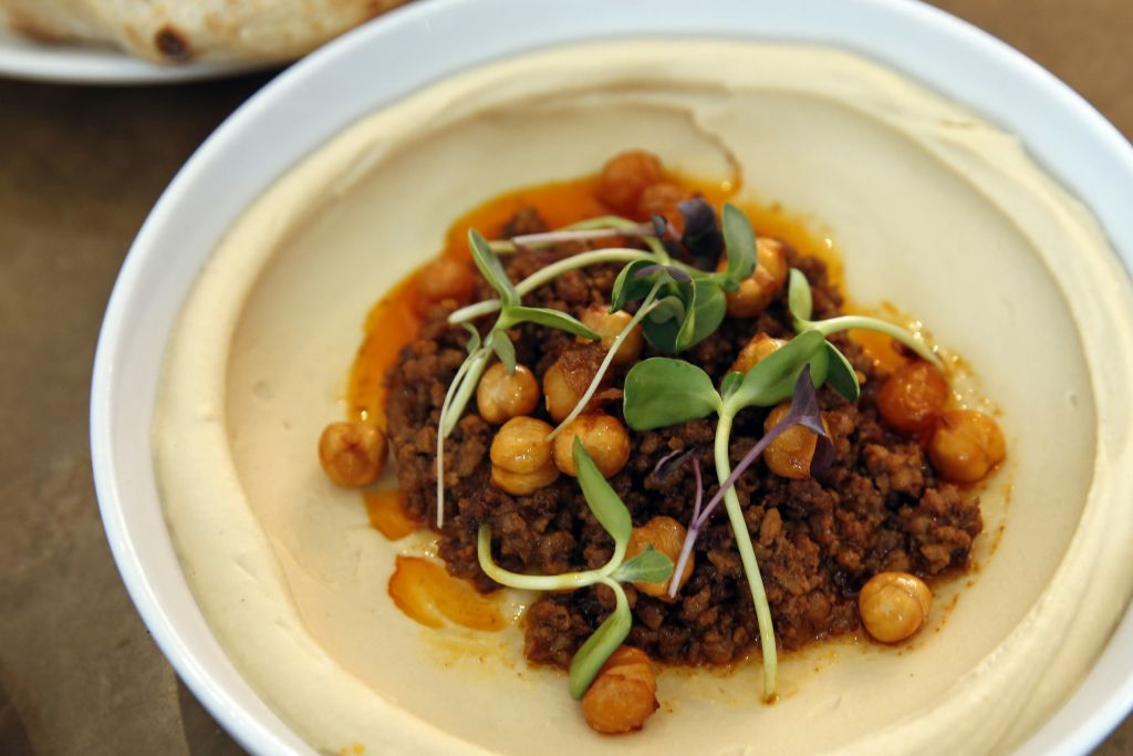 In this Tuesday, May 31, 2016 photo, lamb ragu hummus with crispy chickpeas, sits on a table at Shaya Restaurant, in New Orleans. (AP Photo/Gerald Herbert)