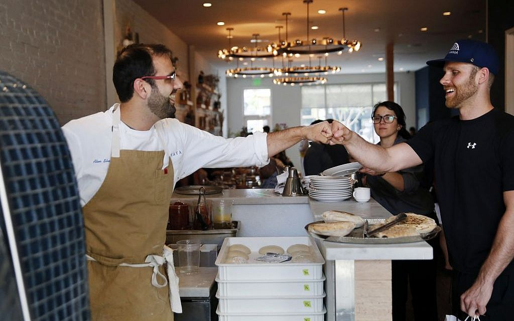 Chef Alon Shaya (left), proprietor of Shaya Restaurant, fist-pumps a customer who complimented him at his restaurant in New Orleans, May 31, 2016. (AP/Gerald Herbert)