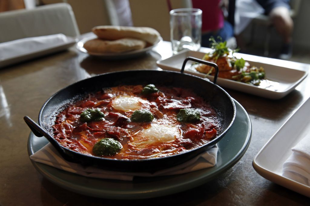 In this May 31, 2016 photo, Shakshouka, which is chermoula, Jerusalem artichokes, spicy chilies, tomato and egg, sits on a table at Shaya Restaurant, in New Orleans. (AP Photo/Gerald Herbert)