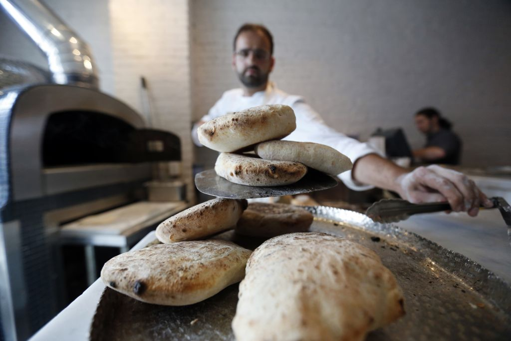 In this Tuesday, May 31, 2016 photo, Chef Alon Shaya, proprietor of Shaya Restaurant, makes house made pita at his wood fired oven at the restaurant in New Orleans. (AP Photo/Gerald Herbert)