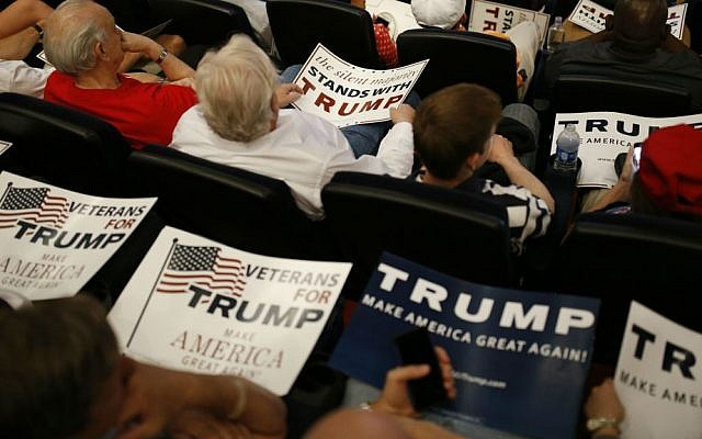 People hold signs as they wait for Republican presidential candidate Donald Trump to speak at the Treasure Island hotel and casino, Saturday, June 18, 2016, in Las Vegas, Nevada. (AP Photo/John Locher)
