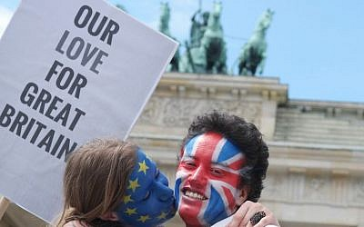 A young couple with faces paint in European, left, and British colors, pose with a sign 'Our Love For Great Britain' during a Kiss Marathon event at Brandenburg Gate in Berlin, Germany, Sunday June 19, 2016 to support the ' Remain' voters in Britain's referendum.  (Joerg Carstensen/dpa via AP)