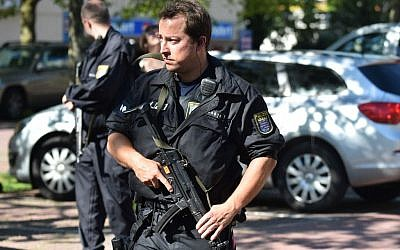 Police officers stand in front of a cinema in Viernheim near Mannheim, southern Germany, Thursday, June 23, 2016, where a gunman was shot after he took hostages in the complex (Boris Roessler/dpa via AP)